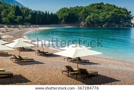 Adriatic sea sand beach at beautiful small bay near the famous Sveti Stefan historical island. Montenegro.