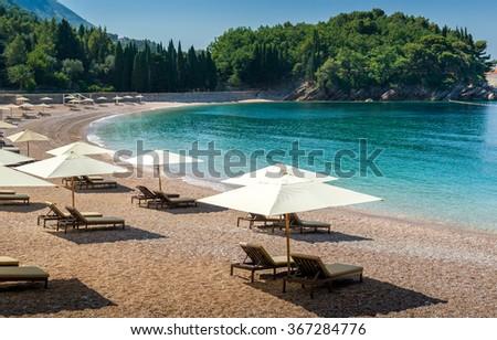 Adriatic sea sand beach at beautiful small bay near the famous Sveti Stefan historical island. Montenegro. - stock photo