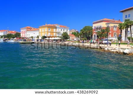 Adriatic sea shore and sunny pier sided by historical buildings, Porec, Croatia - stock photo