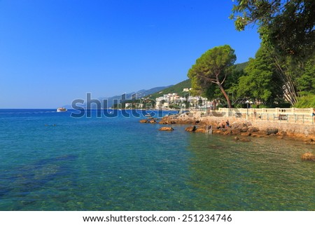 Adriatic sea shore with narrow rocky beach and green trees, Opatija, Croatia - stock photo