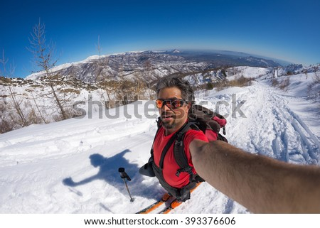 Adult alpin skier with beard, sunglasses and hat, taking selfie on snowy slope in the beautiful italian Alps with clear blue sky. Concept of wanderlust and adventures on the mountain. Fisheye lens. - stock photo