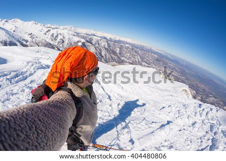 Adult alpin skier with beard, sunglasses and hat, taking selfie on snowy slope in the beautiful italian Alps with clear blue sky. Concept of wanderlust and adventures on the mountain.Fisheye lens. - stock photo