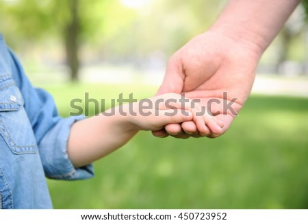 Adult and child hands on natural background