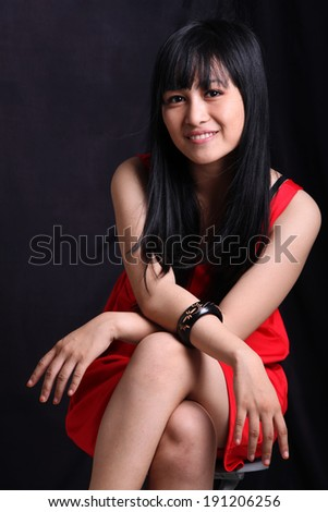 adult asian woman in red dress smiling - stock photo