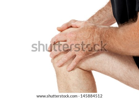 adult attractive man in sportswear knee pain injury ache isolated on white - stock photo