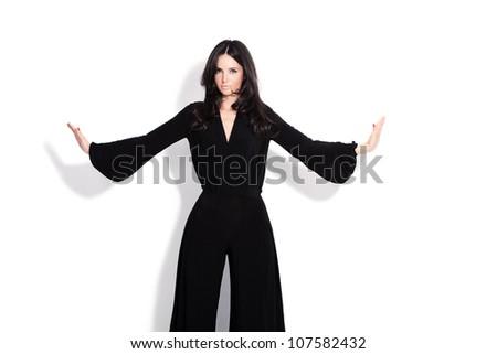 adult beautiful woman in elegant black overalls studio white - stock photo