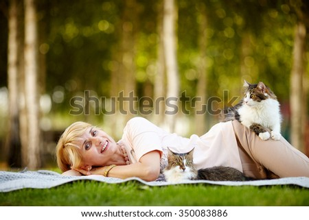 Adult beautiful woman relaxing in the park with their pets. She's on a picnic with 2 cats. - stock photo