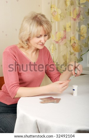Adult blond woman with pills sitting near table