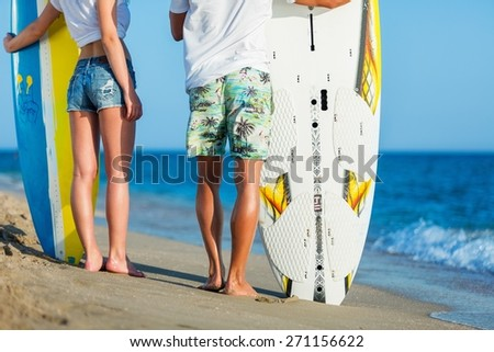 Adult. Brasil latino hispanic couple walking holding hands with surfboard and flag as sarong - stock photo