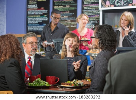 Adult business people in conversation during lunch break - stock photo
