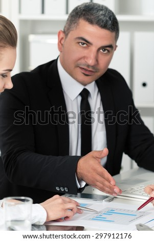 Adult businessman consulting his young female colleague during business meeting. Partners discussing documents and ideas. Focus on hands - stock photo