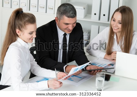 Adult businessman consulting his young female colleagues during business meeting. Partners discussing documents and ideas - stock photo