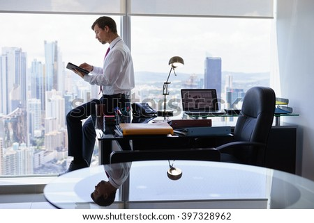 Adult businessman sitting on desk in modern office and reading news on tablet pc. The man works in a skyscraper with a view of the city from the large window. - stock photo