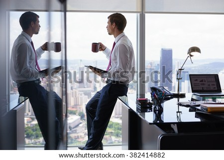 Adult businessman sitting on desk in modern office and reading news on tablet pc with a cup of coffee. The man looks out of the window and contemplates the city and skyscrapers. - stock photo