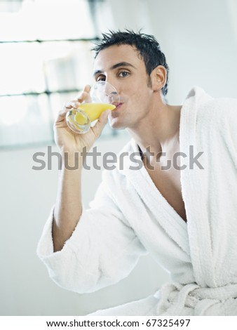 adult caucasian man in white bathrobe drinking orange juice. Vertical shape, waist up, side view - stock photo