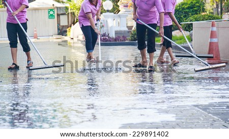 Adult cleaner maid woman with mop and uniform cleaning corridor pass or hall floor of business building. - stock photo