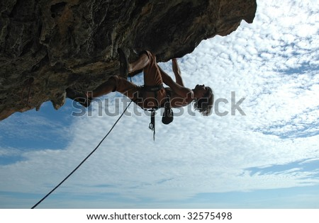 Adult climbing hard overhanging wall in Krabi, Thailand. Silhouette. - stock photo