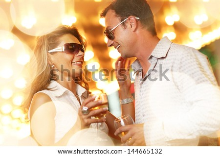 Adult couple enjoying nightlife with glasses of champagne. Shallow DOF. - stock photo
