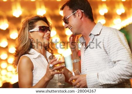 Adult couple enjoying nightlife with glasses of champagne. Shallow DOF. - stock photo