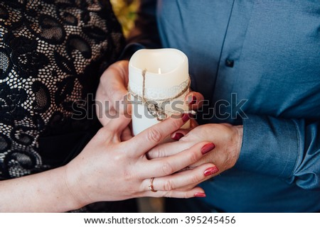adult couple holding hands with a candle.