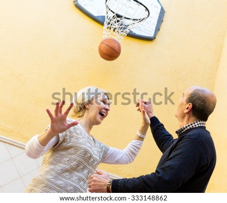 Adult couple playing with ball in yard and laughing - stock photo