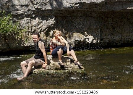 adult Couple relaxing on a rock in the river