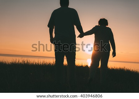 Adult couple silhouettes at sunset. Evening photo. - stock photo