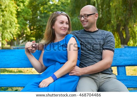 adult couple sit on bench in city park, summer, romantic and love concept, happy people man and woman
