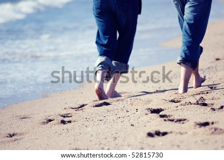 Adult couple walking on beach - stock photo