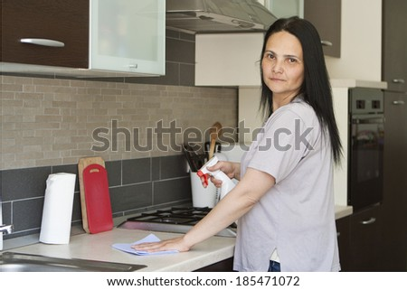 Adult dark haired woman cleaning the table in kitchen, looking at camera