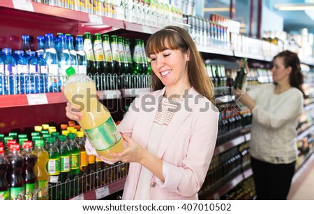 Adult daughter and senior mother selecting cooling beverages at store