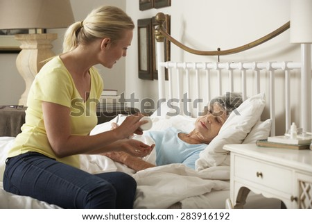 Adult Daughter Giving Senior Female Parent Medication In Bed At Home - stock photo