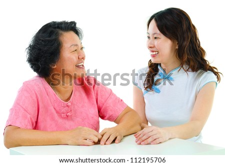 Adult daughter having conversation with senior mother indoor. - stock photo