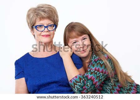 Adult daughter pressed to her elderly mother, white background - stock photo