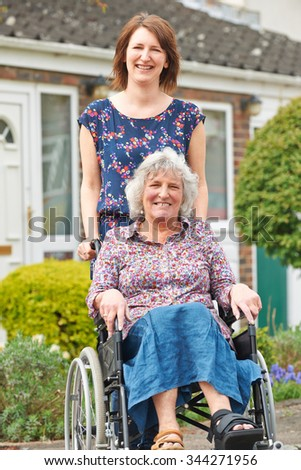 Adult Daughter Pushing Mother In Wheelchair