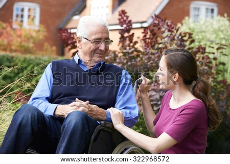 Adult Daughter Visiting Father In Wheelchair - stock photo