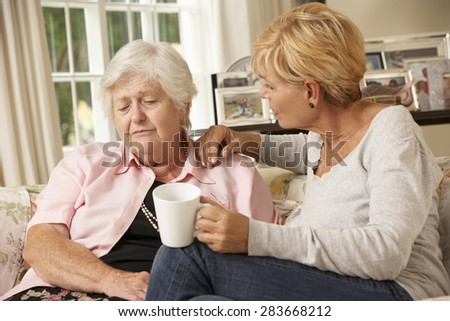 Adult Daughter Visiting Unhappy Senior Mother Sitting On Sofa At Home - stock photo