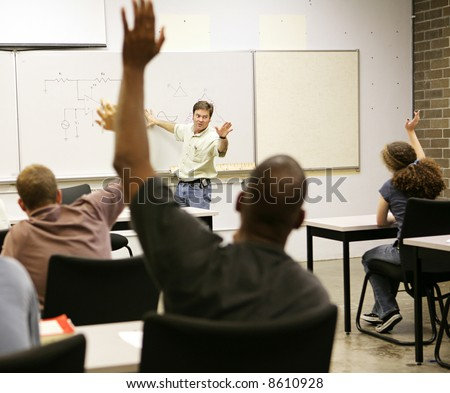 Adult education class raising hands to ask questions. - stock photo
