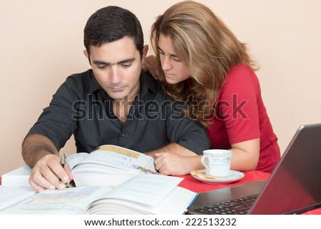 Adult education - Hispanic man and woman studying at home - stock photo