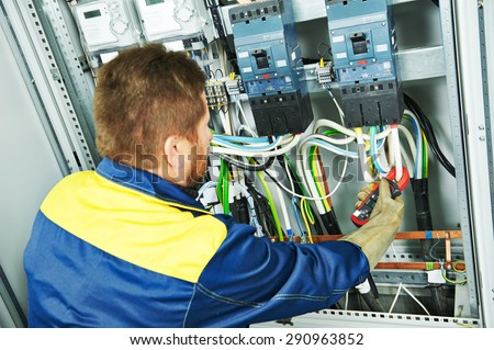 adult electrician builder engineer making electrical measure with equipment in fuseboard - stock photo