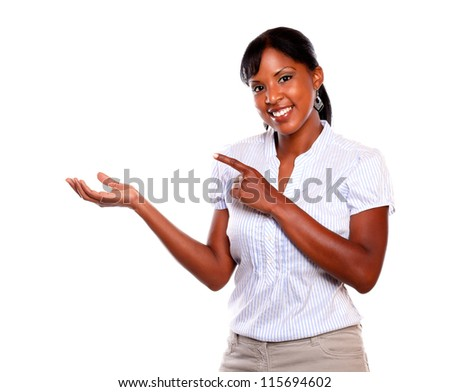 Adult ethic woman looking at you while is pointing to her right on isolated background - stock photo