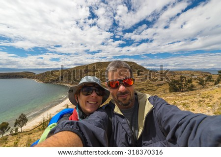 Adult european couple taking selfie in the majestic natural landscape of the Island of the Sun, Titicaca Lake, Bolivia. Concepts of people traveling around the world, wide angle view. - stock photo