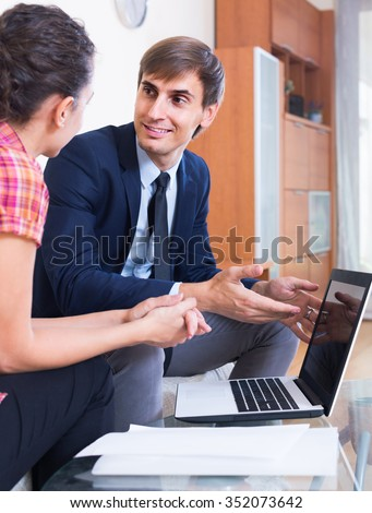 adult european insurance agent and customer discussing agreement terms and smiling - stock photo
