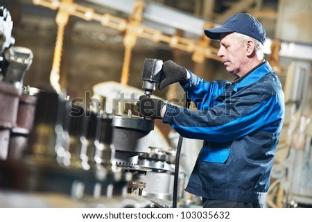 adult experienced industrial worker during heavy industry machinery assembling on production line manufacturing workshop - stock photo