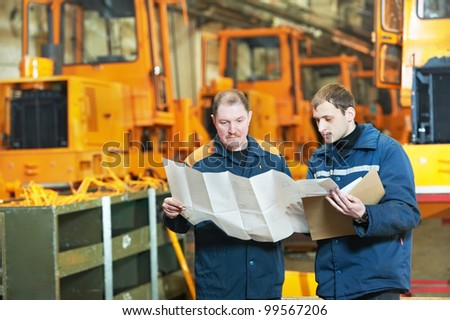 adult experienced industrial workers examining technical drawing during heavy industry machinery assembling on production manufacturing line - stock photo