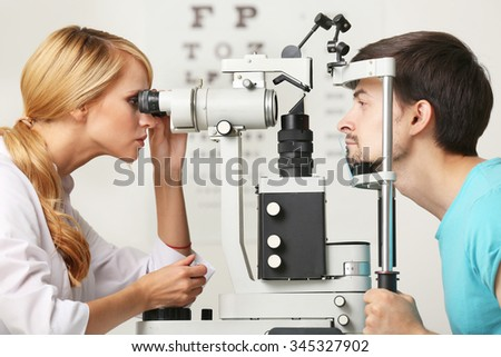 Adult female doctor examing adult male patient - stock photo