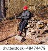 Adult Female Hiker sitting on a pile of timber reading a map - stock photo
