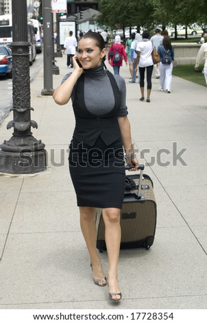 Adult female on black outfit pulling a piece of luggage on a sunny day - stock photo