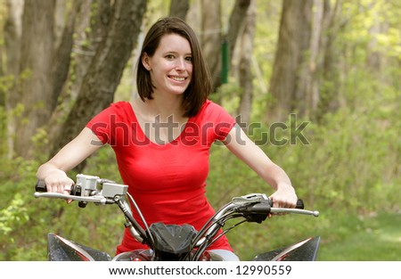 adult female riding an all terrain vehicle, holding handlebars in a natural background