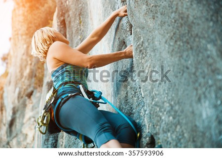 Adult female rock climber on vertical flat wall with poor relief - side view, close-up.  - stock photo